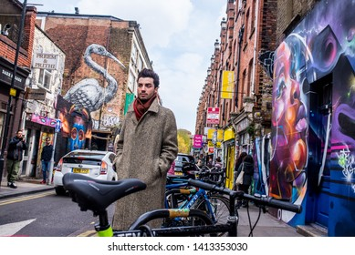 Brick Lane, Shoreditch, London, England, UK - April 2019: Hipster young man wearing long winter coat standing in Brick lane next to a wall covered in graffiti mural street art