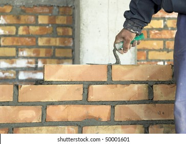 A brick layer putting down another row of bricks