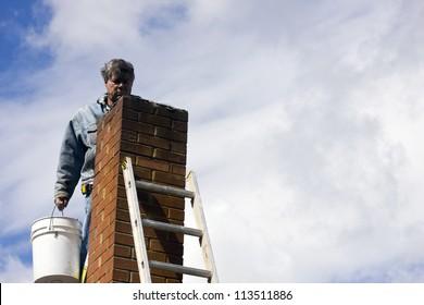 brick mason on a ladder repairing damaged chimney