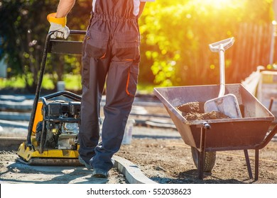 Brick Path Construction. Caucasian Construction Worker with Plate Compactor. Brick Paving Theme.