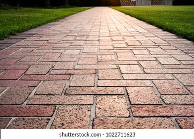 Brick path or sidewalk with perspective going into the distance with soft sunlight reflecting of the bricks. Long paved brick footpath outside with grass.