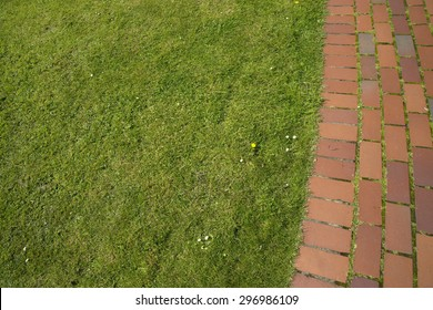 A brick pathway next to a grass area