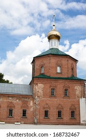Brick red orthodox church with one golden dome