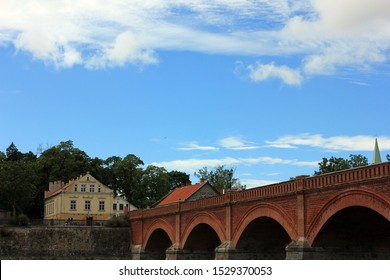 Brick and stone bridge in Kuldiga over Ventas river in Latvia with blue skies and white clouds