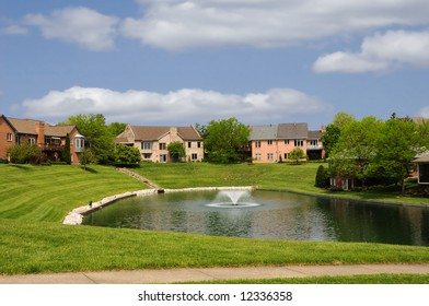 Brick Suburban Homes on a pond in the summer.