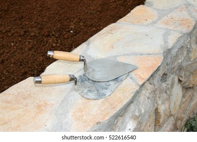 Brick trowels on the sustaining wall under reconstruction