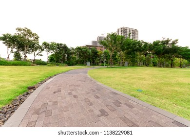Brick walkway and green lawn with white sky in urban park, Bangkok, Thailand for background.
