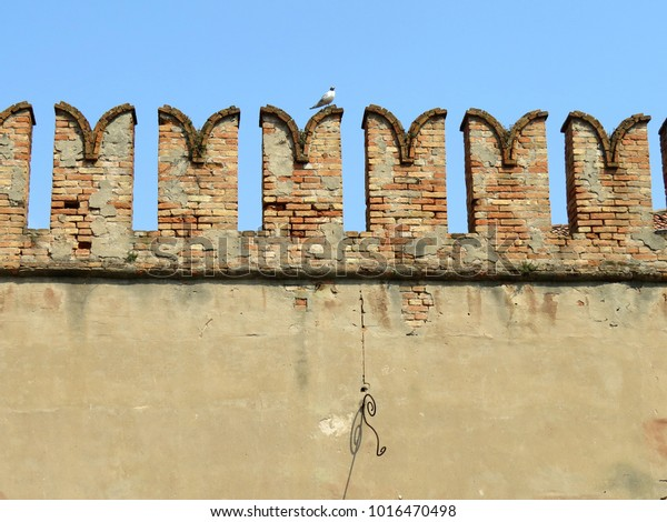 Brick wall against a blue sky in Venice, Italy with seagull