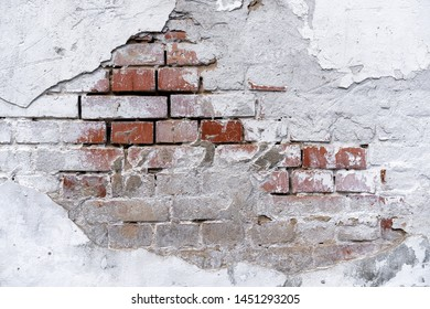 brick wall background with white fallen off plaster. The brick wall is visible from under the white plaster. White stucco and brick wall texture. piece of brick wall under plaster