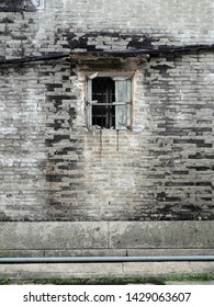 Brick wall black and white patches crumbling mortar with pipes and and old window concrete in Old Beishan Town, Zhuhai; Great Walls of China. Portrait background replacement game textures.