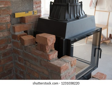 brick wall border for a wood-burning stove or fireplace under construction in the interior fitting area, selected focus