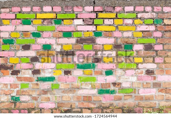 Brick wall with bricks painted in different colors