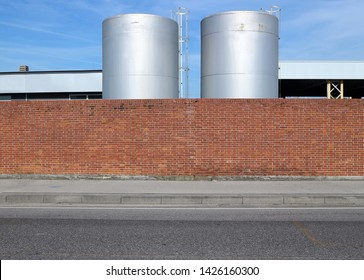 Brick wall with a concrete sidewalk and an asphalt road in front. Tanks for liquid behind. Background for copy space.