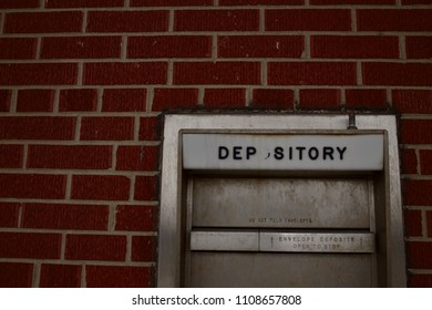 A brick wall with a depository mail slot.