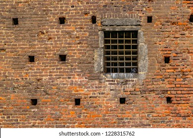 Brick wall exterior view with iron grid window at sforza castle, a touristic attraction medieval fortress located at the historic center of Milan, Italy