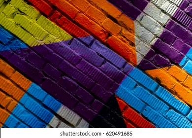 Brick wall with fragment of graffiti, abstract drawings art close-up. For background. Concept of Modern iconic urban culture. Aerosol pictures