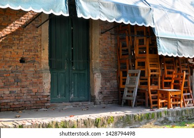 Brick wall, with a green awning and many folding wooden chairs sloppy crowded on an old floor with moss
