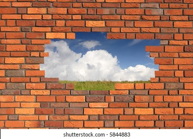 Brick wall with hole revealing grass and clouds