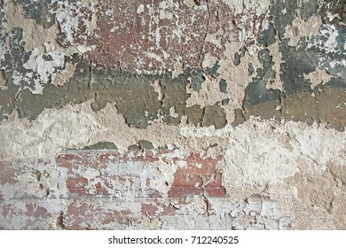 Brick wall. Old flaky white paint peeling off a grungy cracked wall. Cracks, scrapes, peeling old paint and plaster on background of old cement wall. An old cement stone wall as vintage cracked.