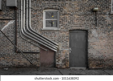 Brick wall with pipes and metal door in an alleyway
