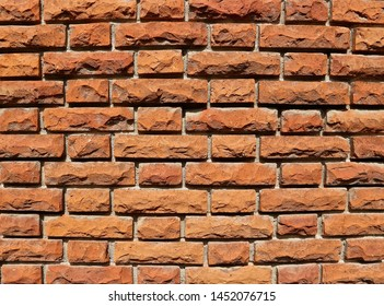 Brick wall with rough and uneven bricks under sunlight. Background and texture, copy space