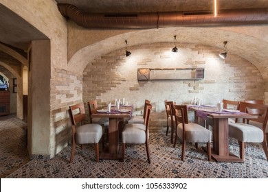 Brick wall and rustic tiled floor in restaurant interior