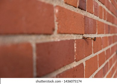 Brick wall with rusty nail sticking out shot at an angle.