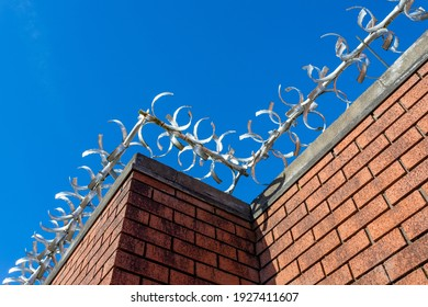 Brick wall with security spikes. Taken on a sunny day showing a strong blue sky as background.