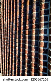 A brick wall in semicircular vertical waves with a hanging metal chain in one side
