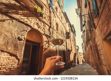 Brick wall streets with wine glass in hand of tourist, ancient town of Tuscany. Historic Centre of Siena, Italy. UNESCO World Heritage Site.