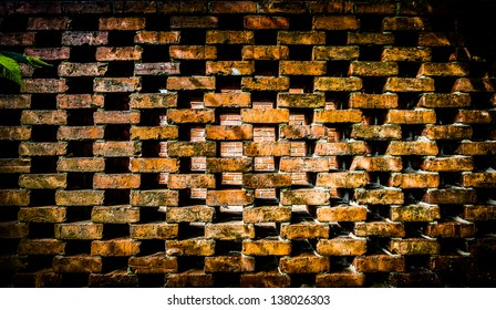 A brick wall with symmetrical spaces throughout. A solid brick wall seen through the gaps.