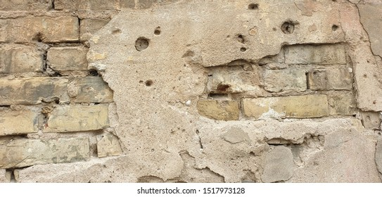 Brick wall with thick crumbled plaster