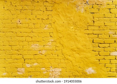 brick wall with an uneven surface painted with yellow paint, fragment