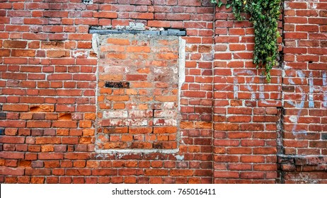 The brick wall, the window is bricked, old cement red brick in the summer in the city, a building that is abandoned.