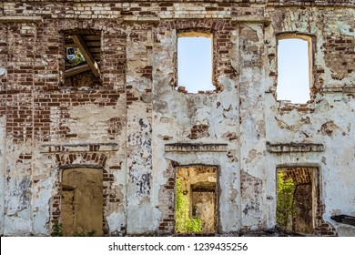 Brick wall with window openings of old abandoned dilapidated historical residential building