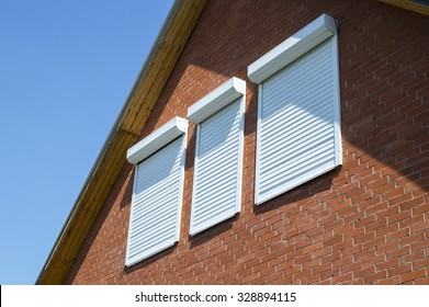 The brick wall and windows with rolling shutters