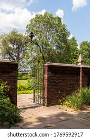 A brick wall with a wrought iron fence gate entrance into the garden in Mellon Park on a summer day, Pittsburgh, Pennsylvania, USA