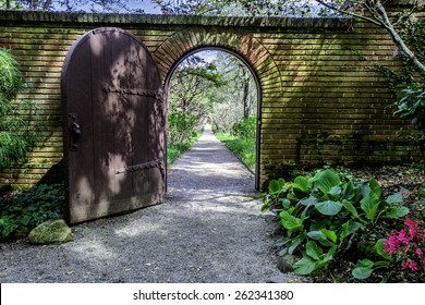 brick walled English garden arch gate that opens to a tree lined path in an english garden that goes on forever