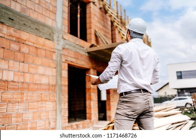 brick walls, infrastructure on construction site. construction engineer reading plans, working on building construction site.