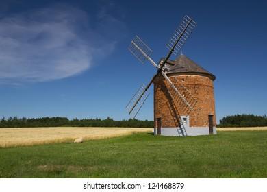 Brick windmill in a field of corn. Blue sky in the background. (Chvalkovice, Czech Republic)