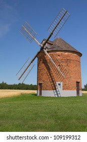 Brick windmill in a field of corn and the green grass.. Blue sky in the background. (Chvalkovice, Czech Republic)