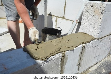 Bricklayer builder laying autoclaved aerated concrete blocks, aac.  Autoclaved aerated concrete blocks walling installation with concrete glue
