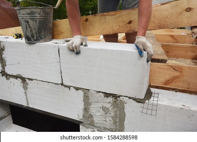 Bricklayer builder laying autoclaved aerated concrete blocks, aac for new house wall.