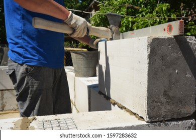 Bricklayer builder laying autoclaved aerated concrete blocks, aac for new house wall.  Autoclaved aerated concrete blocks walling installation