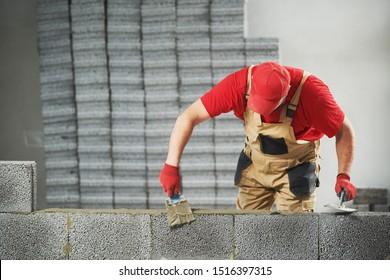 constructor de capas de ladrillo trabajando con bloques de hormigón de cerámica. Amarramiento