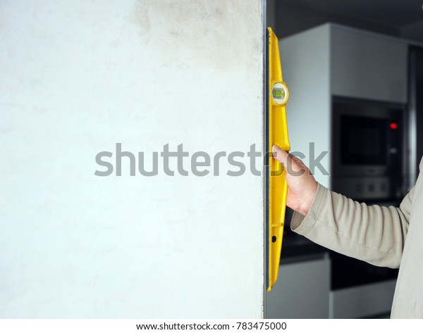 Bricklayer checking the vertically of the door frame with level tool