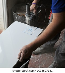 Bricklayer cutting white porcelain stoneware tiles with tile cutter machine, works of the house reform