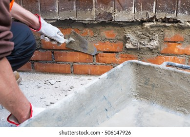 Bricklayer, home repair. A construction worker holding a trowel trowel putty knife while installing red bricks