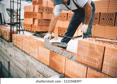 Bricklayer industrial worker installing brick masonry on exterior wall with trowel putty knife