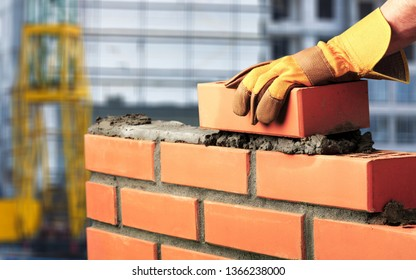 Bricklayer industrial worker installing brick masonry